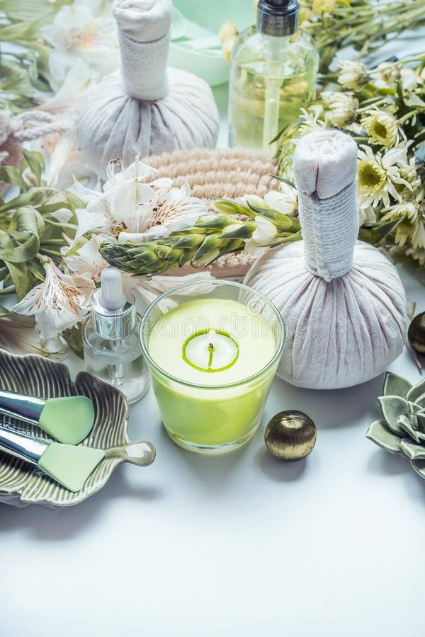 Herbal spa, wellness and massage setting with green flowers and herbs, candle and body skin care accessories stock images