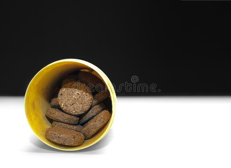 Herbal Supplement Pills in a Yellow Plastic Container on Black and White Background.  royalty free stock photography