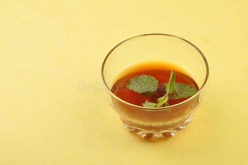 Herbal tea. With leaves on handmade mat stock image