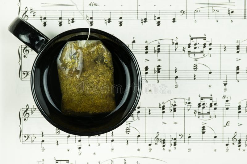 Herbal tea and tea bag in black cup standing at the sheet with musical notes as background. stock photo