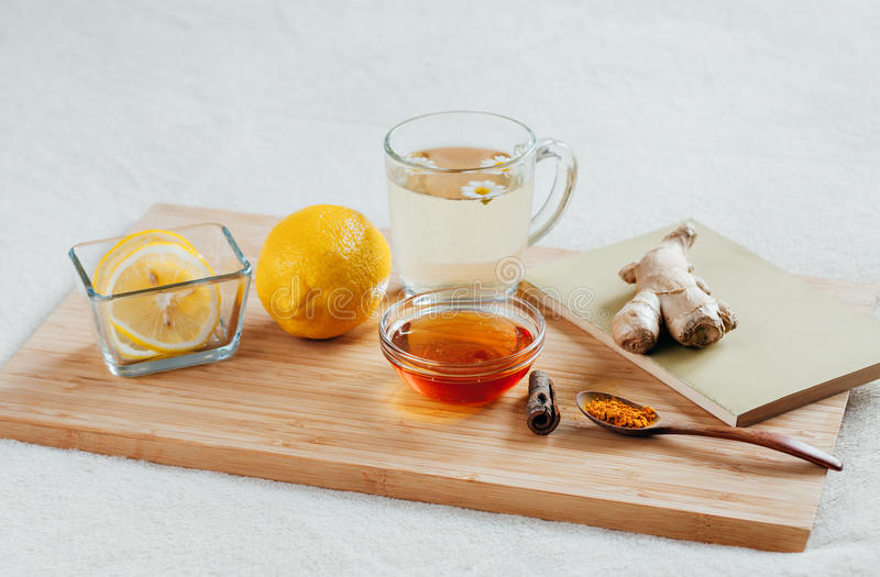 Herbal tea with chamomile flowers, turmeric and honey on a wooden board. Treatment of hot drink ginger. folk remedies royalty free stock image