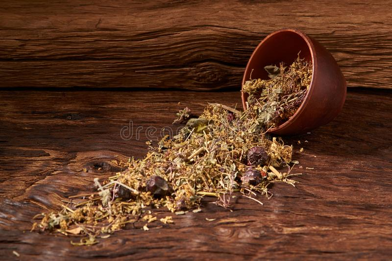 herbal tea in clay bowl on wooden table on black background. selective focus stock photo