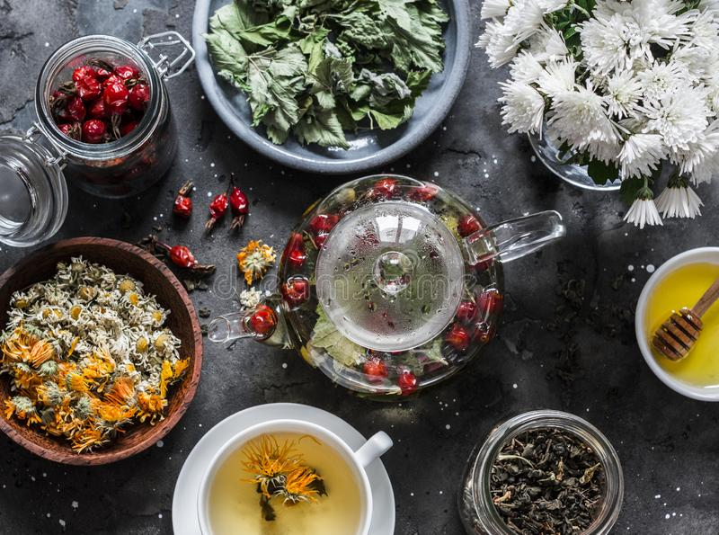 Herbal tea with currant, mint, raspberry leaves, chamomile and calendula flowers, rose hips, teapot on a dark background, top view stock images
