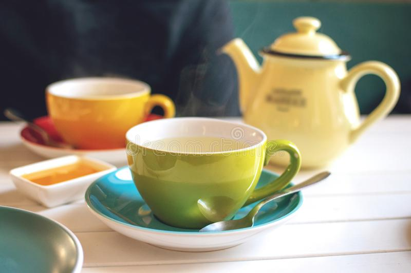Herbal tea in green cup, honey and yellow teapot on white wooden table in cafe. A cup of hot tea with steam. Natural light royalty free stock photo
