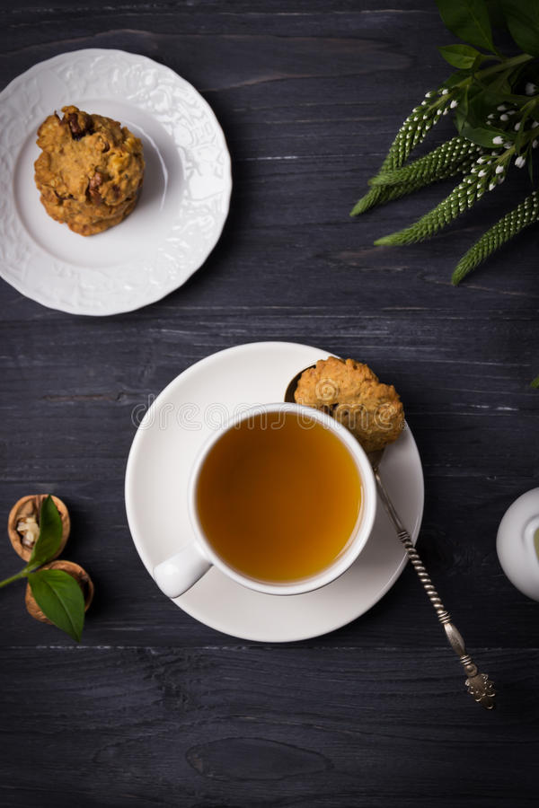 Herbal tea and homemade oatmeal nut cookies on a dark wooden background. Top view royalty free stock photo