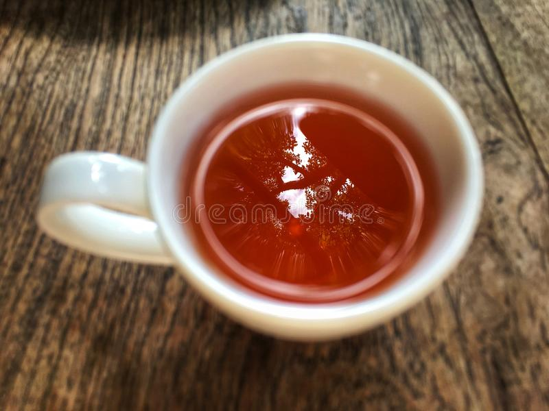Herbal tea inside blur white cup top view on wooden table. stock photo