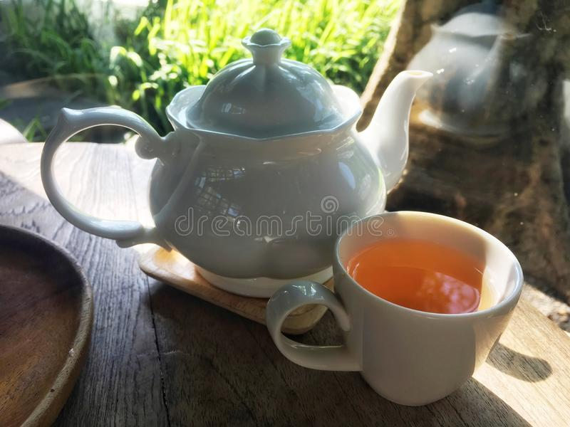 Herbal tea inside white cup and luxury white jar on wooden table. royalty free stock photography