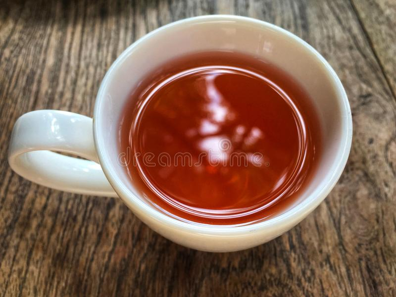 Herbal tea inside white cup top view on wooden table. stock photo
