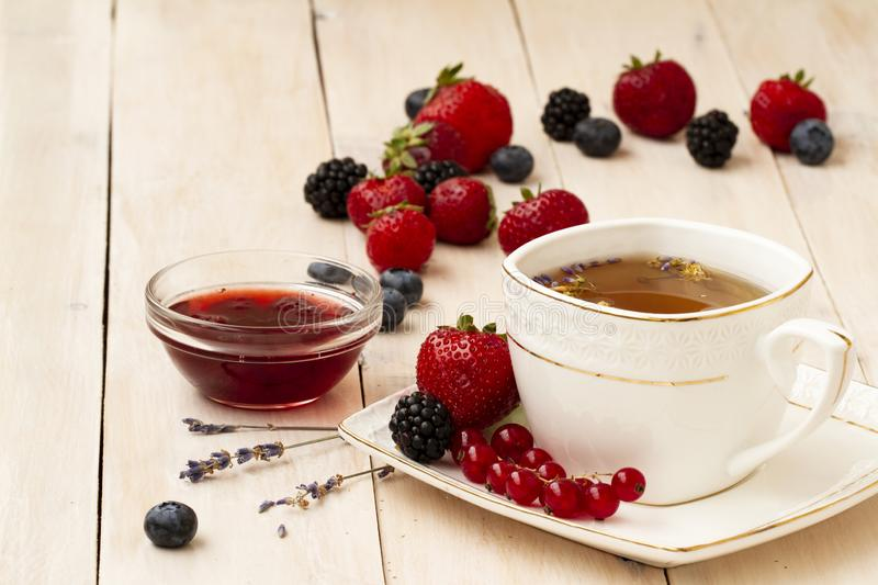 Herbal tea with lavender and mint, homemade jam, fresh strawberries, blackberries and blueberries on a white wooden royalty free stock photo