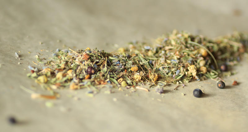 Herbal tea. Leaves and flowers scattered on the parchment closeup zoom view. Shallow depth of field. Kitchen royalty free stock photography