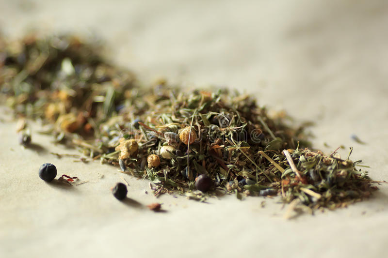 Herbal tea. Leaves and flowers scattered on the parchment closeup zoom view. Shallow depth of field. Kitchen royalty free stock photo