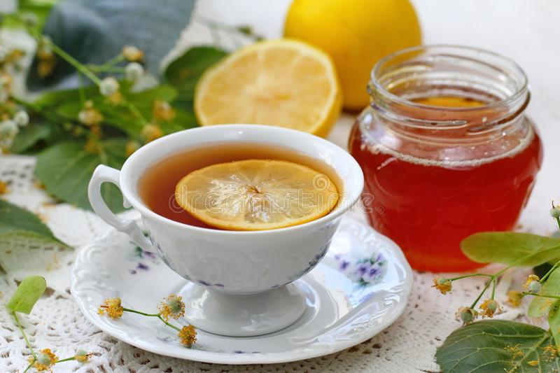 Herbal tea with linden flowers, honey and lemon stock images