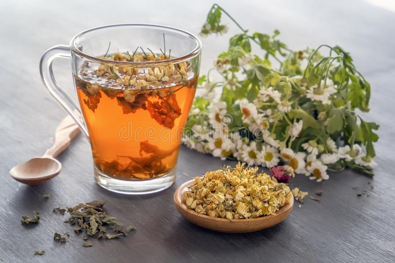Herbal tea with pharmaceutical chamomile on wooden table. Close-up royalty free stock photos