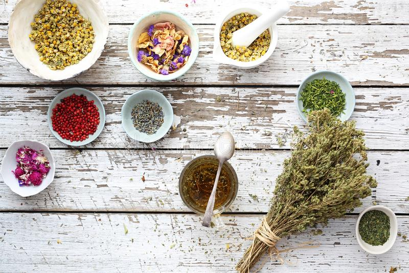 Herbal tea. Traditional, natural health infusions. Herbal first aid kit. A composition of herbs, flowers and spices. Healthful potions and infusions on a wooden royalty free stock image