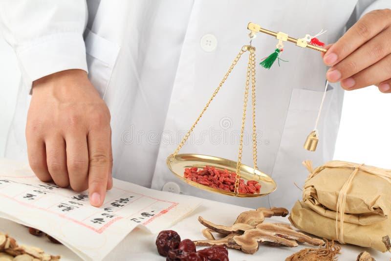 Herbalist asiatico che pesa le erbe medicinali cinesi fotografia stock