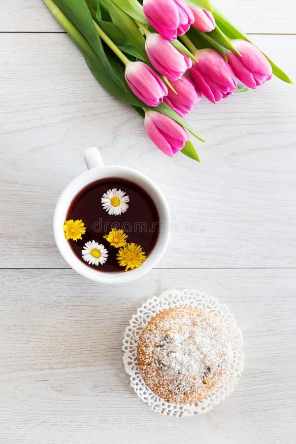Herbata i s?odka bu?eczka z zielonymi wypiekowymi fili?ankami z tulipanami zdjęcia stock