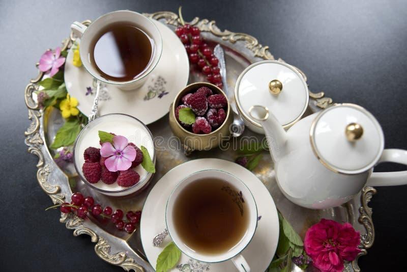 Herbata w starych porcelan filiżankach, panakota deserze i malince na starej srebnej tacy, retro obraz stock