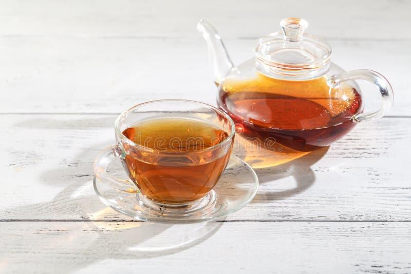 Herbata w szkle z herbatą warzy w szklanym dzbanku umieszczającym na ta fotografia stock