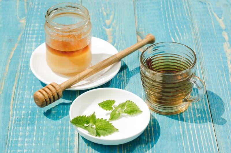 herbata z mennicą i miodem na drewnianym błękita stole Selekcyjnej ostro?ci wizerunek fotografia royalty free