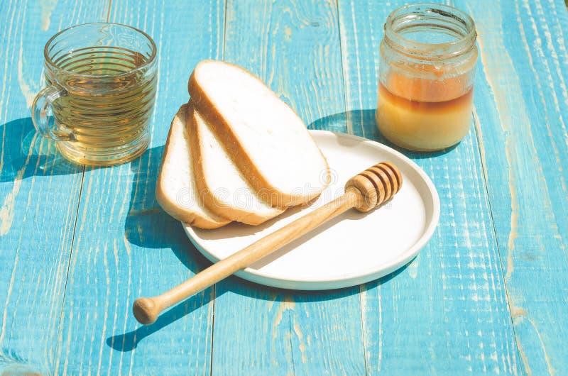 herbata z miodem i rżnięci biali ciasto plasterki na drewnianym błękicie zgłaszamy tło obraz stock