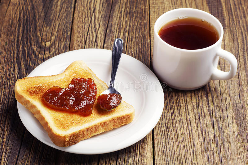 Herbaty i grzanki chleb z dżemem w kształcie serca obrazy stock