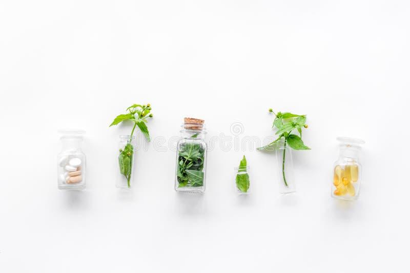 Herbe médicinale dans des bouteilles sur le copyspace blanc de vue supérieure de fond images libres de droits