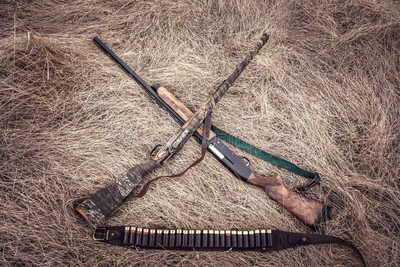 Herbe sèche de fusils de chasse de chasse sur la meule de foin comme fond de chasse dans le style occidental sauvage photo libre de droits