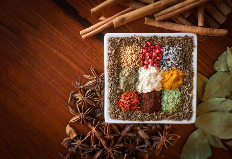 Herbes colorées et graines sèches d'épices décentrées sur le fond en bois photos libres de droits