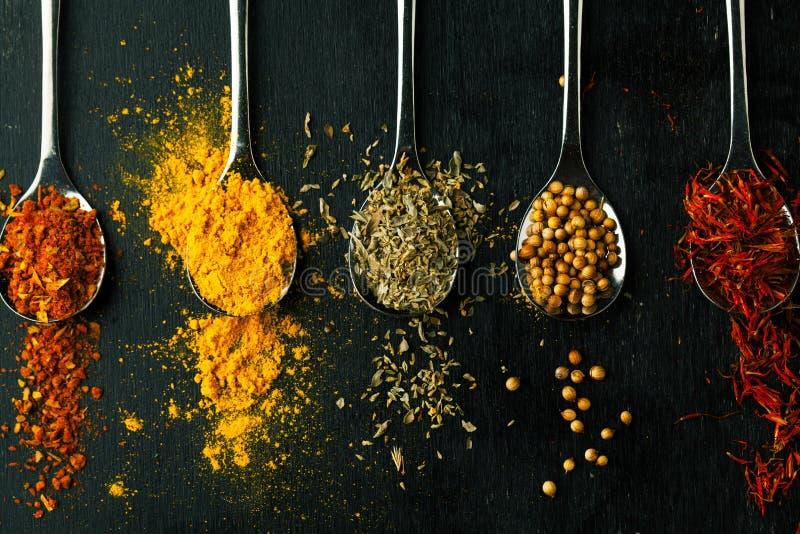 Herbes et condiments d'épices sur une table dans une cuillère photos stock