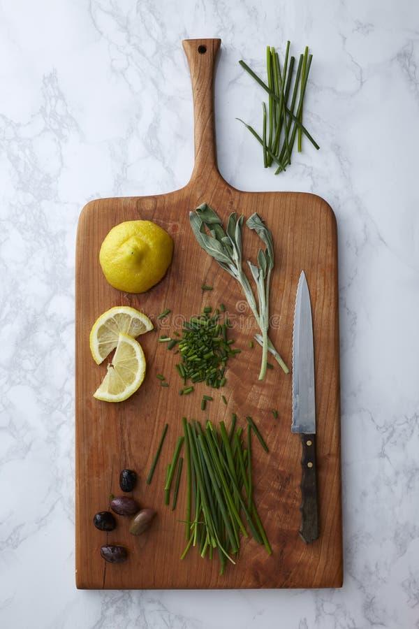 Herbes, olives et citrons étant coupés et préparés sur une planche à découper en bois photographie stock