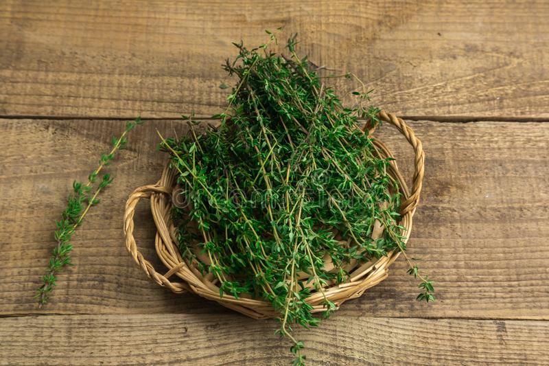 Herbs in a basket on a wooden background stock photo