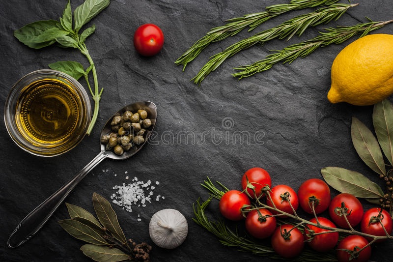 Herbs mix with tomatoes, lemon and olive oil on the black stone table stock image
