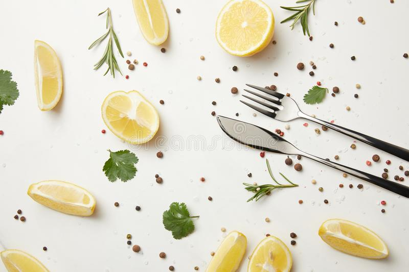 Herbs and pepper with fork and knife isolated on white stock image