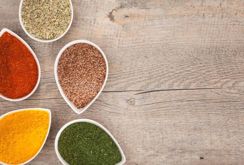 Herbs and Spices. Colourful ground or dried herbs and spices with copy space to the side. Includes Turmeric, Cayenne Pepper, Dill, Flax seed and Fennel stock photo