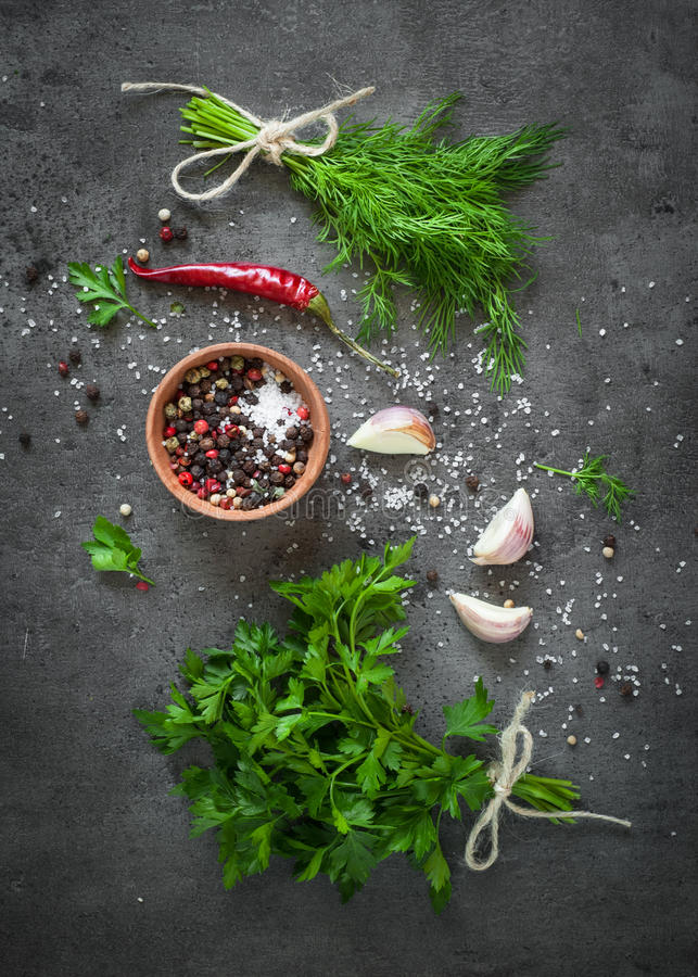Herbs and spices at dark table. stock photos