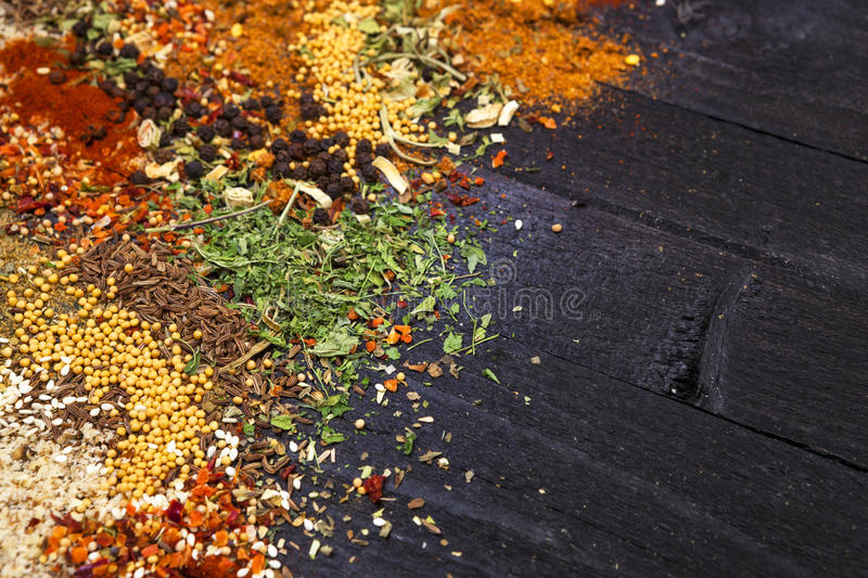 Herbs and spices over black wooden background. Top view with copy space royalty free stock photography