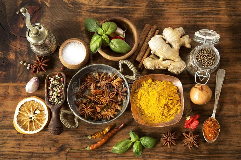 Herbs and spices. Various herbs and spices on wooden background stock photos