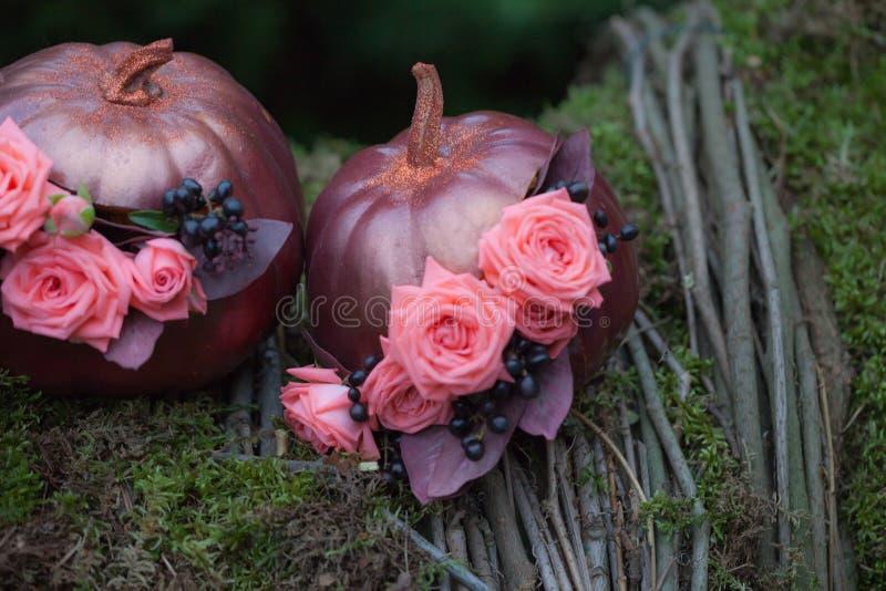 Herbst Décor mit Blumenstrauß von Rosen und von Trauben im goldenen Kürbis Stilvolle Halloween-Dekorationen Glänzende dekorative stockfoto