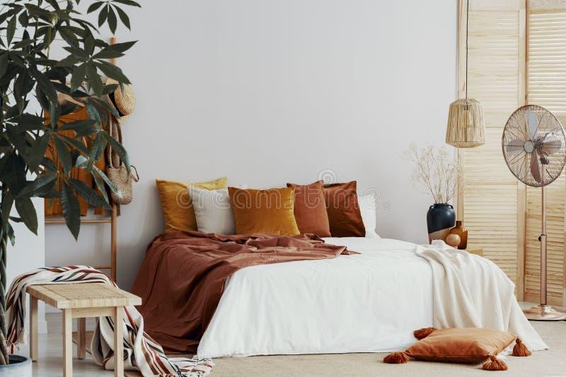 Herbst färbte Kissen auf Königgrößenbett im schicken Schlafzimmerinnenraum lizenzfreie stockfotografie