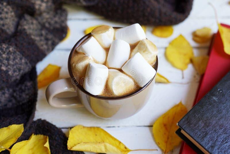 Herbst flatlay mit Tasse Kaffee, Schal, gelben Blättern und Büchern auf weißem hölzernem Hintergrund lizenzfreies stockbild
