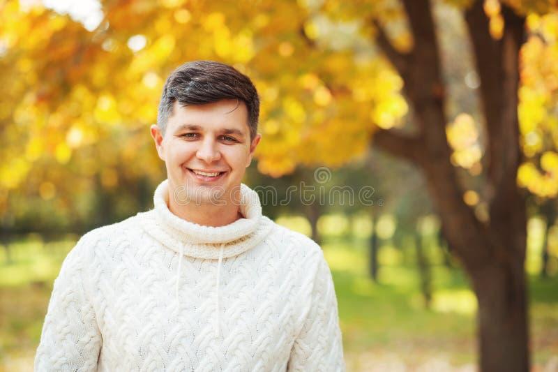 Herbst kommt! Seien Sie heute glücklich! Schließen Sie herauf Porträt des jungen hübschen Brunettemannes, der beim Herbstparkläch lizenzfreie stockfotos