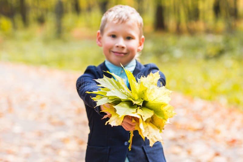 Herbst-, Natur- und Leutekonzept - jugendlich haltener Blumenstrauß des hübschen Jungen vom Herbstlaub und vom Lächeln stockfotos
