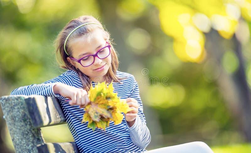 Herbst Porträt eines lächelnden jungen Mädchens, das in ihrer Hand einen Blumenstrauß von Herbstahornblättern hält stockfotografie