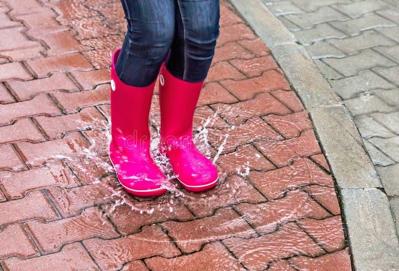 Herbst Schutz im Regen Mädchen, das rosa Gummistiefel trägt und in eine Pfütze springt stockfoto