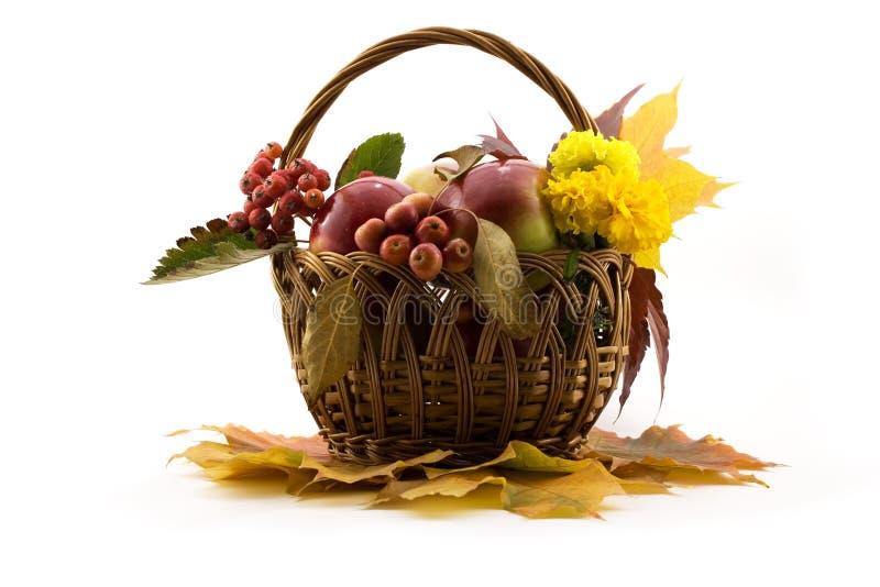 Herbst trägt mit gelben Blättern in einem Korb Früchte lizenzfreie stockbilder