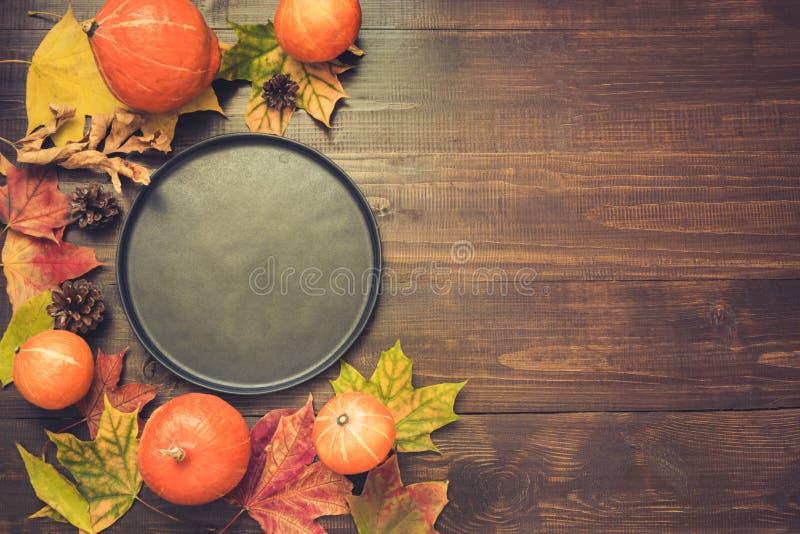 Herbst- und Danksagungstagesgedeck mit gefallenen Blättern, Kürbisen, schwarzer Servierplatte und Weinlesetischbesteck auf Braun lizenzfreie stockfotos
