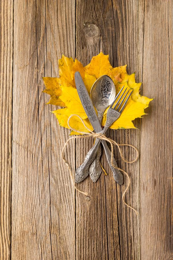 Herbstabendessengedeck für Erntedankfest mit bunten Ahornblättern auf rustikalen hölzernen Brettern stockbilder