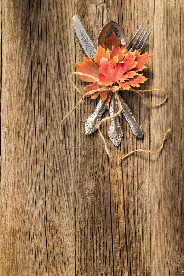 Herbstabendessengedeck für Erntedankfest mit bunten Ahornblättern auf rustikalen hölzernen Brettern lizenzfreie stockfotos