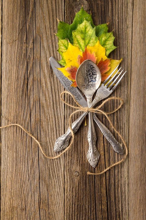 Herbstabendessengedeck für Erntedankfest mit bunten Ahornblättern auf rustikalen hölzernen Brettern stockfoto
