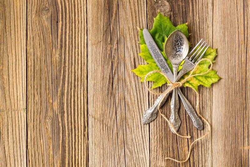 Herbstabendessengedeck für Erntedankfest mit bunten Ahornblättern auf rustikalen hölzernen Brettern lizenzfreie stockfotografie